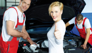 Mechanics works on engine bay, customer shows thumb up